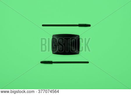 Close Up Set Of Face Makeup Black Mascara Brushes And Eye Shadows Over Green Background, Elevated To