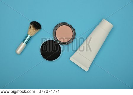 Close Up Set Of Face Makeup Blush, Beige Sponge, Foundation And Brush Over Blue Background, Elevated