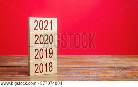 Businessman Builds Wooden Blocks 2018, 2019, 2020, 2021. The Concept Of The Beginning Of The New Yea