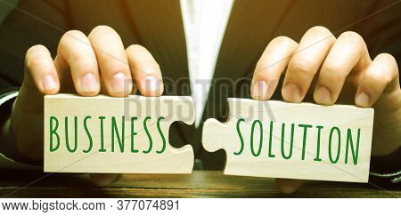 A Businessman Holds Wooden Puzzles With The Words Business Solution. The Concept Of Solving Problems