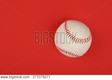 Close Up One New Baseball Ball With Red Stitch Over Vivid Red Background, Elevated Top View, Directl
