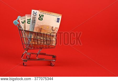 Close Up Several Different Value Euro Paper Currency Banknotes In Small Shopping Cart Over Red Backg