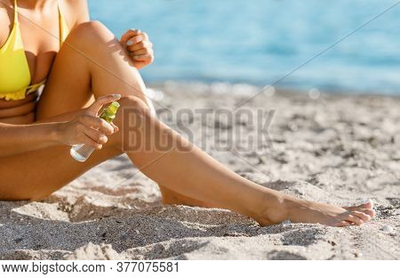 Sunbathing And Uv-protection. Girl Applying Tanning Lotion On Smooth Legs Sitting On Beach At Seasid