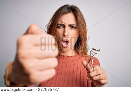 Young beautiful brunette woman using eyelash curler over isolated white background annoyed and frustrated shouting with anger, crazy and yelling with raised hand, anger concept