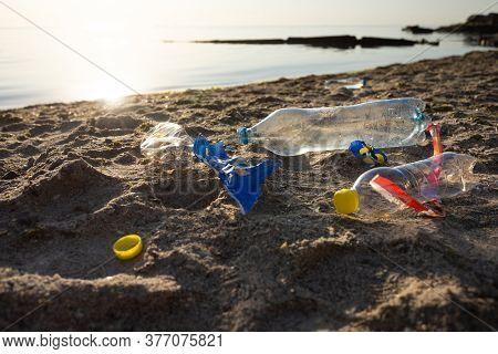 Beach Pollution Concept. Plastic Litter Trash Lying On Sand Near Sea Polluting Seashore. Ecological