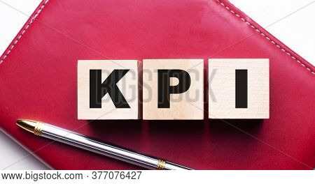 Kpi Is Written On Wooden Cubes On A Burgundy Notebook Near The Pen. Business Concept