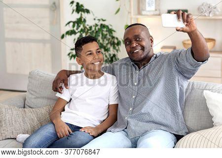 Bonding With Grandchildren. Happy Black Grandpa Taking Selfie On Smartphone With His Grandson While
