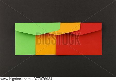 Close Up Group Of Three Colorful Mail Envelopes, Green, Yellow And Red, Over Grey Paper Background,