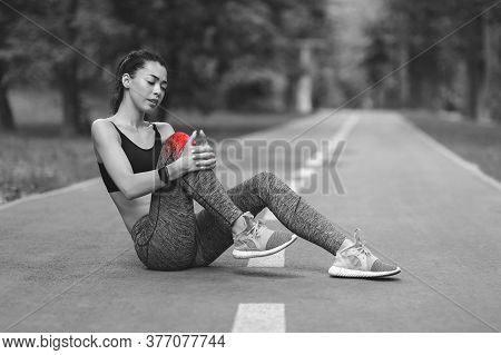 Knee Pain. Young Sporty Asian Girl Suffering From Leg Trauma During Jogging In Park, Bw Image With R