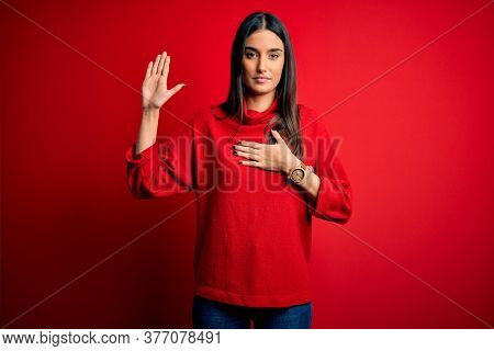 Young beautiful brunette woman wearing casual sweater over isolated red background Swearing with hand on chest and open palm, making a loyalty promise oath