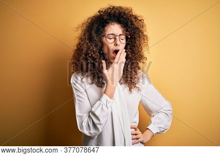 Young beautiful brunette woman with curly hair and piercing wearing shirt and glasses bored yawning tired covering mouth with hand. Restless and sleepiness.