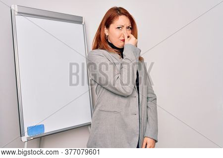 Young beautiful redhead businesswoman doing business presentation using magnetic board smelling something stinky and disgusting, intolerable smell, holding breath with fingers on nose. Bad smell