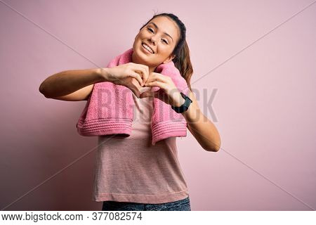 Young beautiful brunette sportswoman wearing sportswear and towel over pink background smiling in love doing heart symbol shape with hands. Romantic concept.