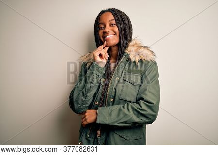 Young african american woman wearing winter parka coat over isolated background looking confident at the camera with smile with crossed arms and hand raised on chin. Thinking positive.
