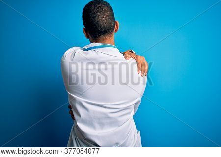 Handsome african american doctor man wearing coat and stethoscope over blue background Hugging oneself happy and positive from backwards. Self love and self care