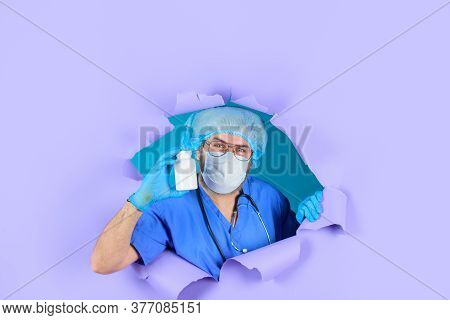 Doctor In Medical Mask With Pills. Pharmaceutical Drug. Bearded Doctor. Doctor Holds Pills. Through