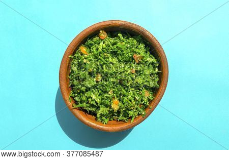 Famous Traditional Arabic Cuisine. Tabbouleh Green Salad In A Brow On Bright Blue Background. Top Vi