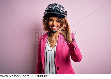 African american motorcyclist woman with curly hair wearing moto helmet over pink background smiling positive doing ok sign with hand and fingers. Successful expression.
