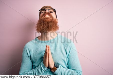 Handsome Irish redhead man with beard wearing glasses over pink isolated background begging and praying with hands together with hope expression on face very emotional and worried. Begging.