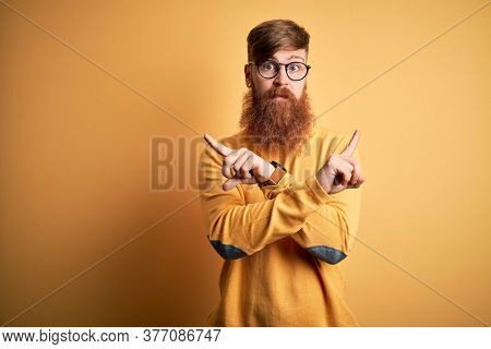 Handsome Irish redhead man with beard wearing glasses over yellow isolated background Pointing to both sides with fingers, different direction disagree