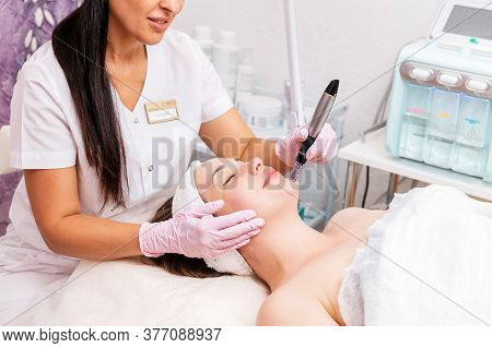 Beauty Salon. Smiling Cosmetologist In Rubber Gloves Makes Fractional Mesotherapy Of The Face To The