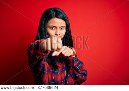 Young beautiful chinese woman wearing casual shirt over isolated red background Punching fist to fight, aggressive and angry attack, threat and violence