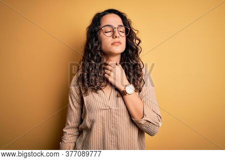 Beautiful woman with curly hair wearing striped shirt and glasses over yellow background Touching painful neck, sore throat for flu, clod and infection