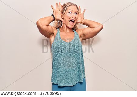 Middle age caucasian blonde woman wearing sportswear smiling cheerful playing peek a boo with hands showing face. surprised and exited