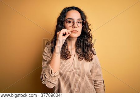Beautiful woman with curly hair wearing striped shirt and glasses over yellow background mouth and lips shut as zip with fingers. Secret and silent, taboo talking