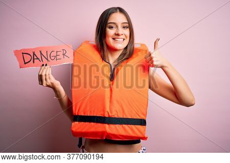 Young beautiful brunette woman wearing lifejacket holding paper with danger message happy with big smile doing ok sign, thumb up with fingers, excellent sign