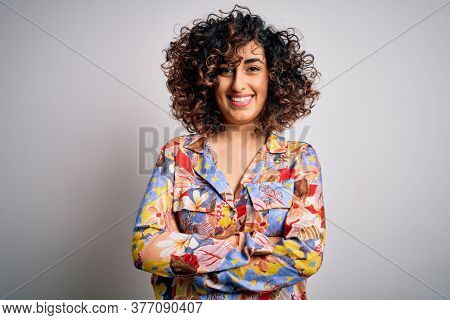 Young beautiful curly arab woman wearing floral colorful shirt standing over white background happy face smiling with crossed arms looking at the camera. Positive person.
