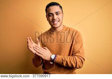 Young brazilian man wearing casual sweater standing over isolated yellow background clapping and applauding happy and joyful, smiling proud hands together