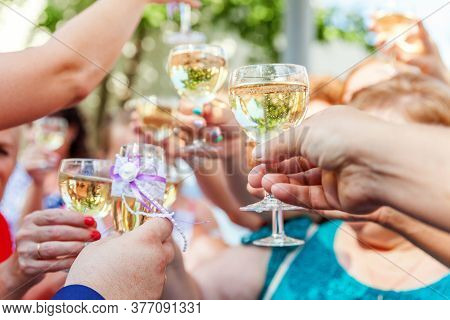 Cheers. Group Of People Drinking And Toasting In Restaurant. Hands Holding Glasses Of Champagne And
