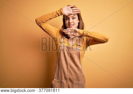 Young beautiful blonde girl wearing overall standing over yellow isolated background Smiling cheerful playing peek a boo with hands showing face. Surprised and exited