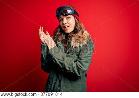 Young blonde girl wearing ski glasses and winter coat for ski weather over red background clapping and applauding happy and joyful, smiling proud hands together