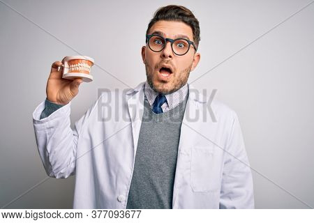 Young dentist man with blue eyes holding orthodontic dental prosthesis over isolated background scared in shock with a surprise face, afraid and excited with fear expression