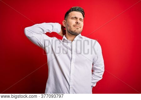 Young business man with blue eyes wearing elegant shirt standing over red isolated background Suffering of neck ache injury, touching neck with hand, muscular pain