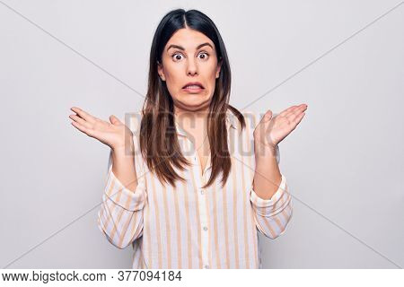 Young beautiful brunette woman wearing casual striped shirt standing over white background clueless and confused with open arms, no idea and doubtful face.