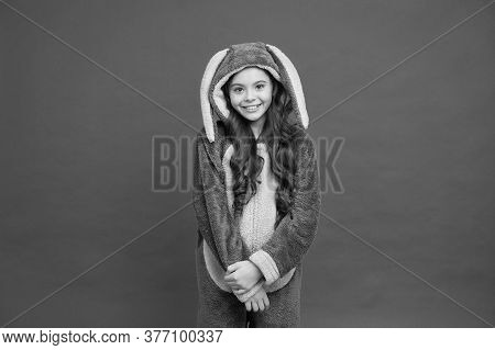 Happy Girl In Bunny Pajamas. Lifestyle Concept. Rest And Relax. Cute Bunny Kid On Red Background. Ba