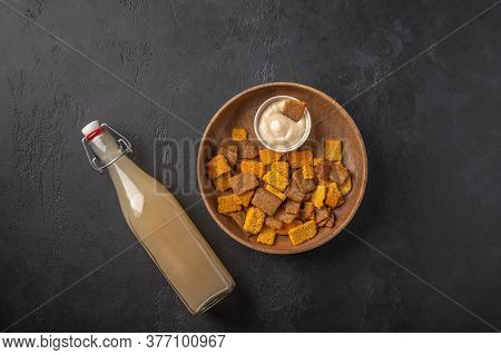 Top View Homemade Tradishional Russian Light Rye Kvass In Bottle And Crackers On Dark Wooden Backgro
