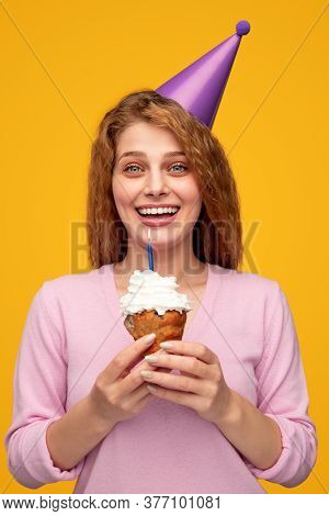 Delighted Young Female In Party Cap Showing Cupcake With Candle And Smiling For Camera During Birthd