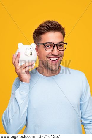 Positive Young Man In Glasses Listening To Clinking Of Coins And Smiling For Camera While Shaking Pi