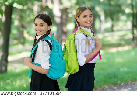 Positive Mood. Teenage Girls With Backpacks Walking In Park. Back To School. Teen Kids With Backpack
