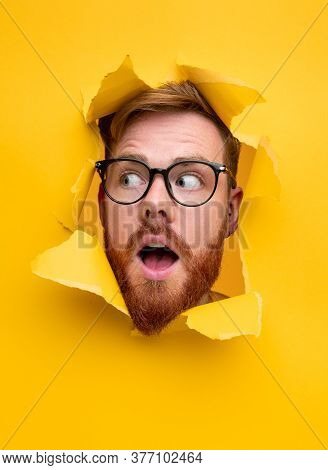 Astonished Redhead Guy In Glasses Looking Away With Opened Mouth While Peeking Out From Hole In Brig