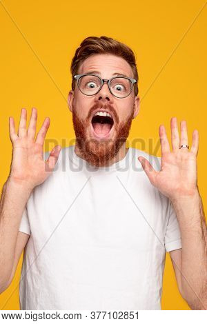 Astonished Bearded Male In White T Shirt Looking At Camera And Shouting Against Yellow Background