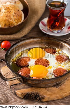 Traditional Turkish Breakfast - Fried Egg With Turkish Sausage. Bread, Tomato And Tea