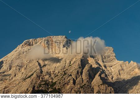 The Top Of The Seekofel With The Shadow Of Two Passing Clouds And The Small Moon In The Center Of A