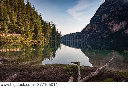 The Warm Morning Light Illuminates The Numerous Green Pines That Are Reflected In The Water Of The B