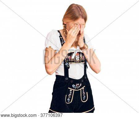 Young beautiful blonde woman wearing oktoberfest dress rubbing eyes for fatigue and headache, sleepy and tired expression. vision problem