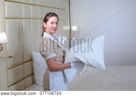 Maid Service In The Hotel Room. Cleaning Of Hotel Rooms. A Girl In Uniform Holds A Pillow. Change Of